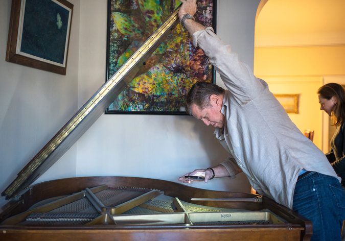 Mr. Berman inspects a baby grand piano that is not moving with Dr. Harrison-Ross to her new digs. Credit Emon Hassan for The New York Times